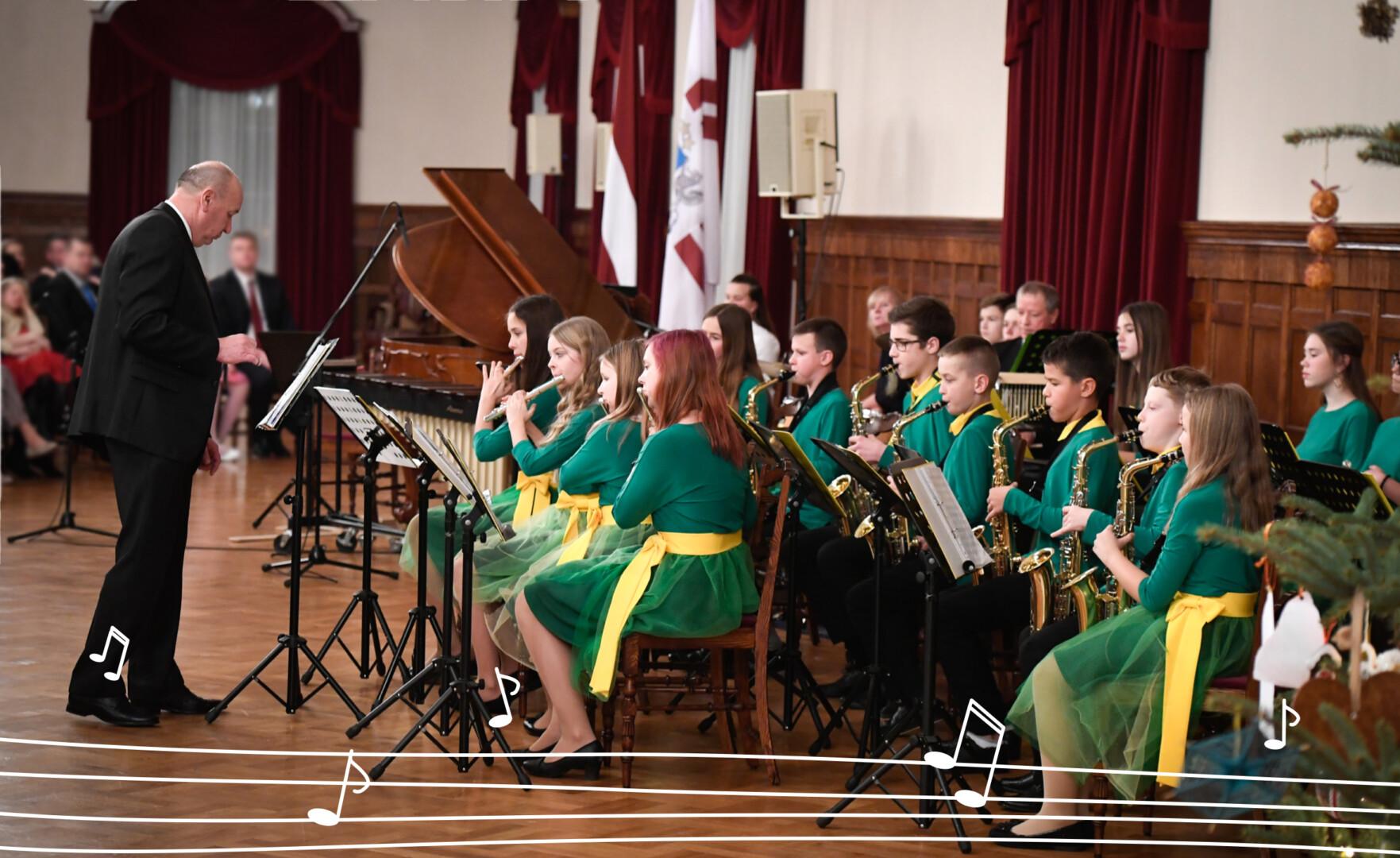Bērnu orķestris Ziemassvētku koncertā spēlē dažādus instrumentus